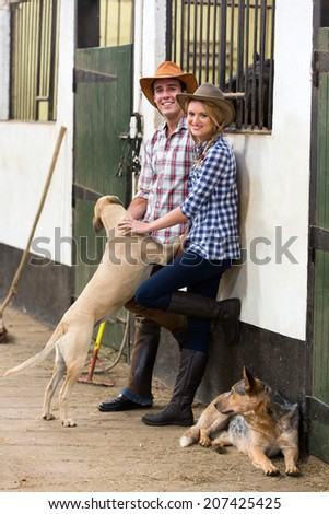 young horse farming couple and their dogs in stables - stock photo