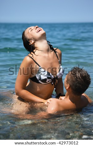 young hot woman sitting astride man in sea near coast