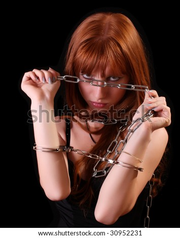Young hot woman with handcuffs and chain on her hand on black background - stock photo