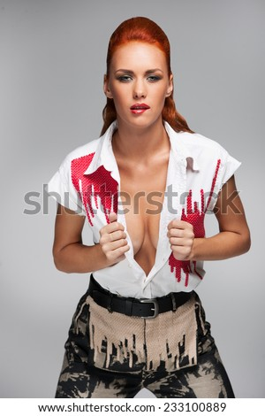 Young hot woman with open shirt on grey background. closeup on pretty redhead girl showing her cleavage. - stock photo