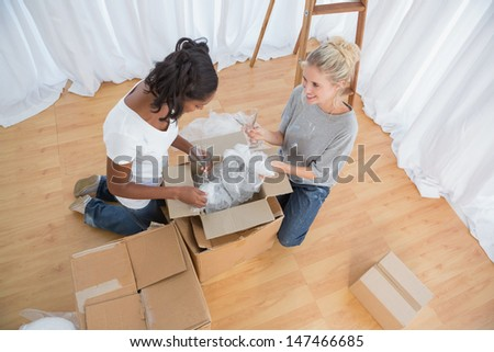 Young housemates unpacking in new home and chatting together - stock photo