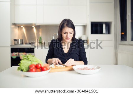 Young housewife beginner cook crying while cutting onion.Slice,dice and chop onion.Stinging eyes and tears when cutting onions to prepare dinner.Shedding tears and wiping with the back of her hand - stock photo