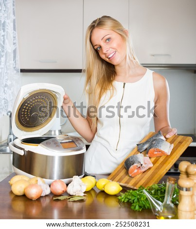Young housewife cooking salmon with new electric multicooker at home  - stock photo