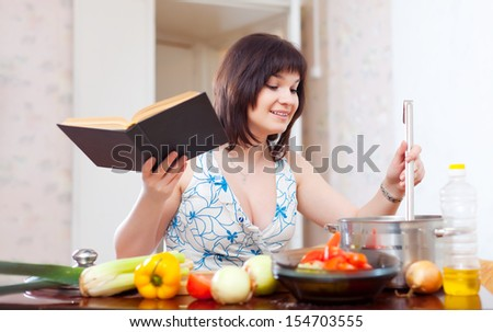 Young housewife cooking with cookery book in kitchen