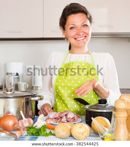Young housewife cooks meat with rice at home - stock photo