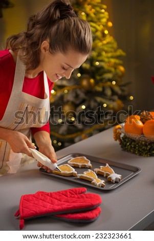 Young housewife decorating christmas cookies with pastry bag - stock photo
