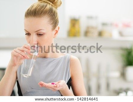 Young housewife eating pills and drinking water - stock photo