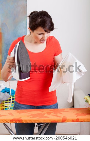 Young housewife has a problem with iron - stock photo