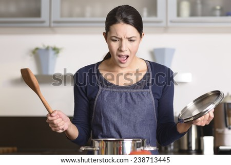 Young housewife having a calamity in the kitchen reacting in shock and horror as she lifts the lid on the saucepan on the stove to view the contents as she cooks dinner - stock photo
