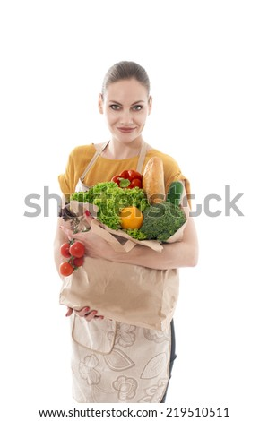 Young housewife  holding a grocery bag full of vegetables, isolated on white background.