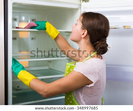 Young housewife in apron and rubber gloves washing fridge parts  - stock photo
