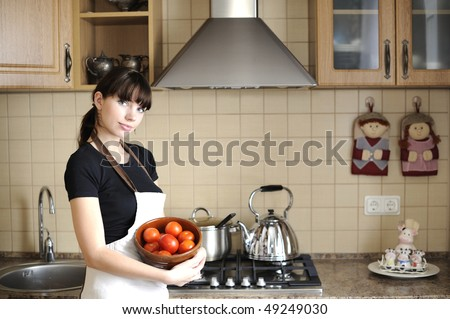 Young housewife in kitchen - stock photo