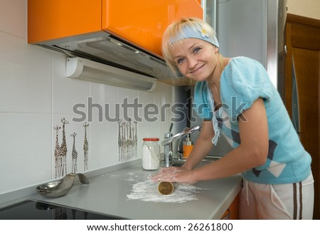 young housewife in modern kitchen making a dough