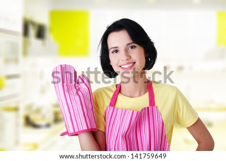 Young housewife in pink apron ang glove at kitchen - stock photo