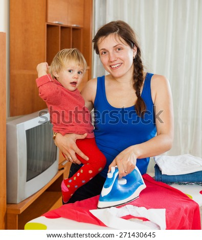 Young housewife ironing clothes on the ironing board with baby
