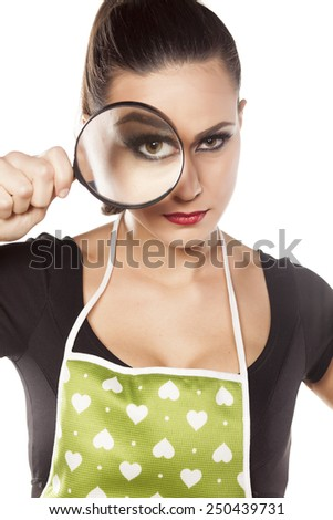 young housewife looking through a magnifying glass - stock photo