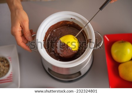 Young housewife making apple in chocolate glaze