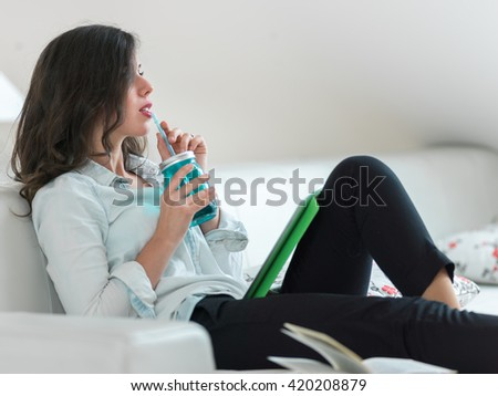 Young housewife sitting on couch using tablet pc and drinking juice