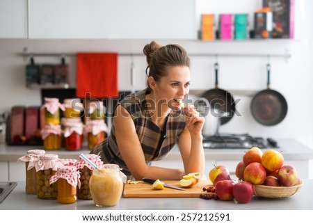 Young housewife standing near jars with fruits jam and eating apple - stock photo