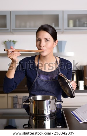 Young housewife tasting her cooking as she prepares the dinner in her kitchen sampling directly from the pot on the hob with a wooden spoon as she looks at the camera - stock photo