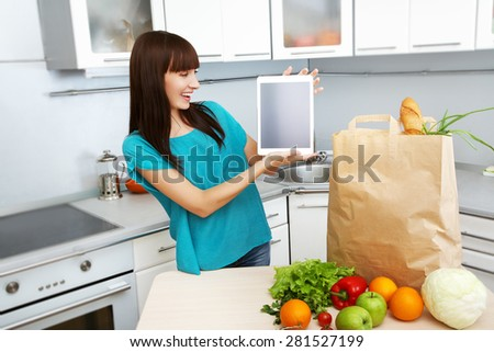 young housewife uses a tablet computer in the kitchen. woman following recipe cooking vegetables on digital tablet. online food shopping - stock photo
