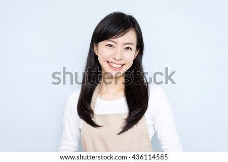 young housewife with apron against blue background - stock photo