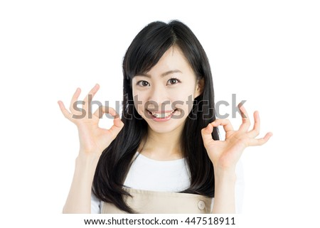 young housewife with apron showing OK gesture isolated on white background