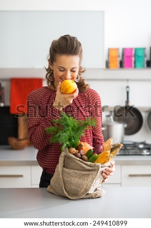 Young housewife with shopping bag of purchases from local market eating apple - stock photo