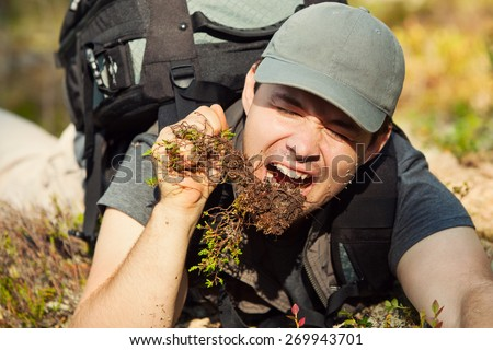 Young hungry man tourist surviving by eating grass and roots in forest. - stock photo