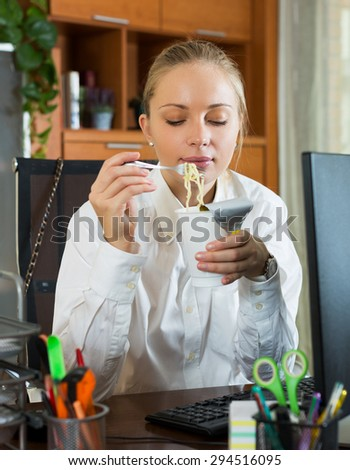 Young hungry woman having fast lunch at office desk - stock photo