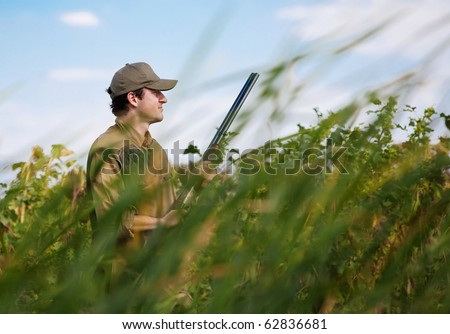 Young hunter camouflaged in dense vegetation during a hunting party - stock photo