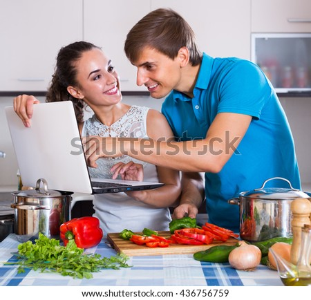 Young husband and wife browsing internet for recipe
