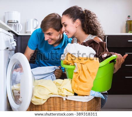 Young husband and wife near washing machine with basket of linen