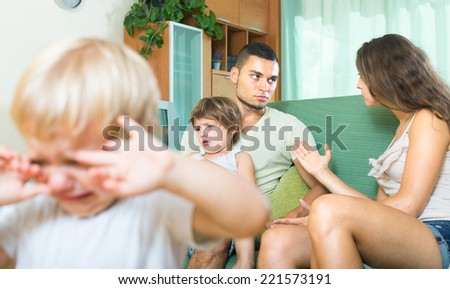 Young husband and wife sitting on the couch and quarreling in the presence of children - stock photo