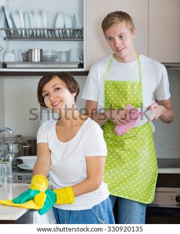 Young husband helping housewife doing regular clean up indoors