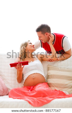 Young husband present jewelery to his pregnant wife - stock photo