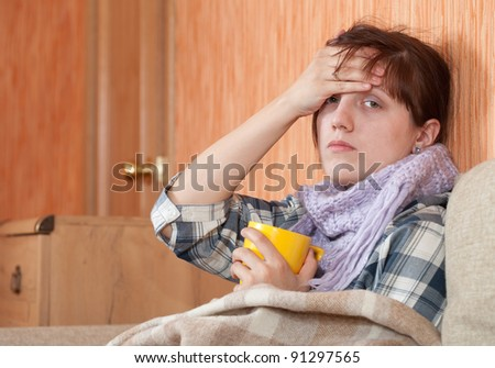 Young illness woman drinking hot tea in blanket - stock photo