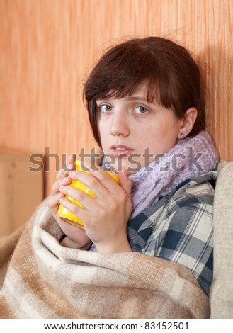 Young illness woman drinking tea in  blanket