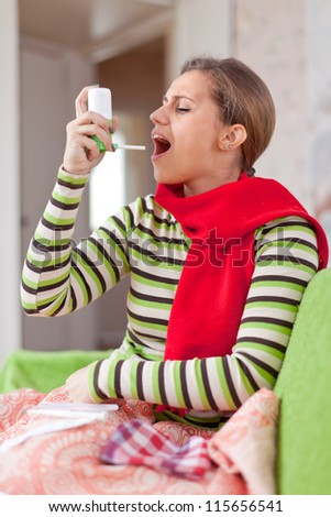 Young illness woman uses spray in home - stock photo