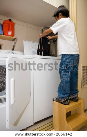 Young independent asian boy doing his own laundry - stock photo