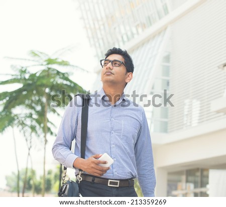 young indian business man on a smartphone light vintage tone - stock photo