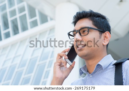 Young Indian business man talking on phone in front modern office building. - stock photo