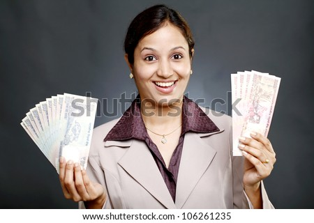 Young Indian business woman holding currency notes