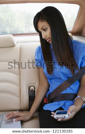Young Indian business woman using laptop in car - stock photo