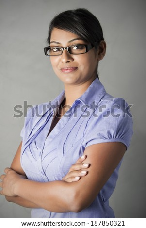 Young Indian Business woman wearing framed glasses with folded arms - stock photo