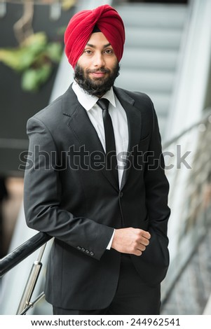 Young indian businessman in turban is looking at camera. - stock photo