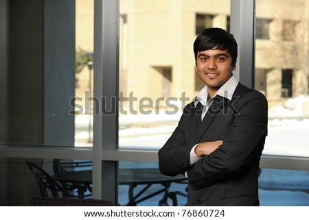 Young Indian Businessman standing up by an office window