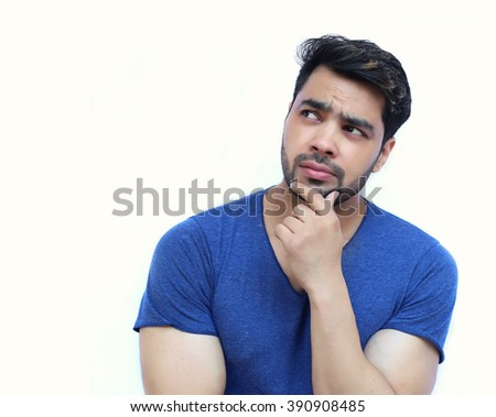 Young Indian Confused Man Scratching His Chin - isolated white background - stock photo