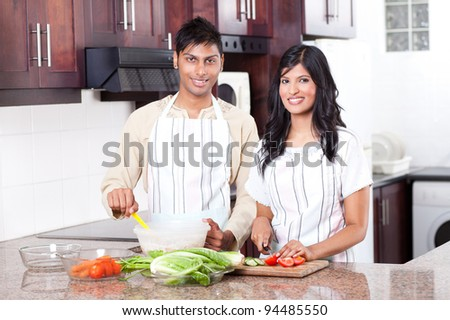 young indian couple cooking in kitchen - stock photo