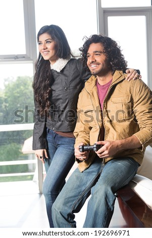 young Indian couple relaxing and playing video games. - stock photo